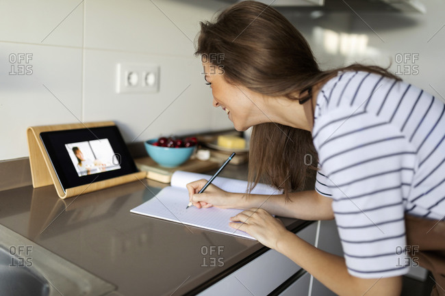 Young woman watching video over digital tablet and writing recipe in book at home
