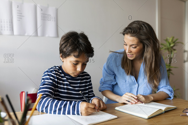 Female tutor assisting boy in writing homework on table at home
