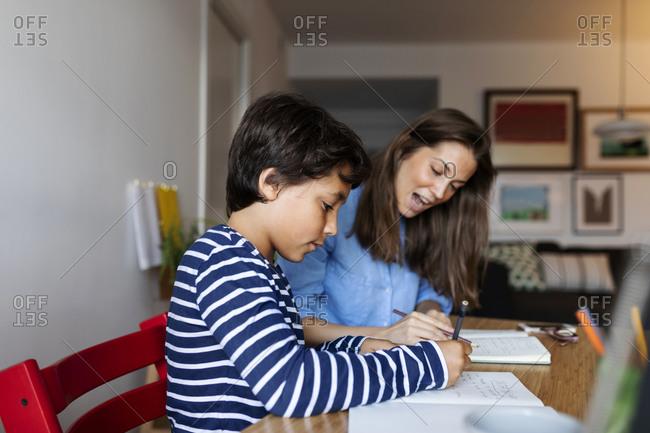 Female tutor explaining her student on table at home