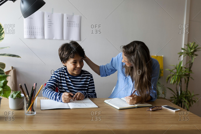 Female tutor talking with smiling boy while sitting at table