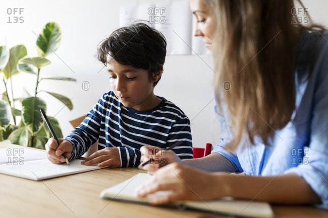 Close-up of female tutor looking at boy writing homework on table