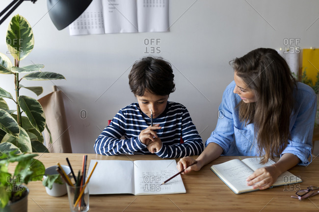 Female tutor explaining to boy through book on table at home