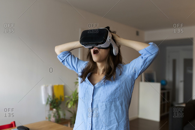 Young woman with mouth open looking through virtual reality simulator while standing in home office