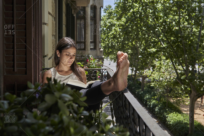 Woman reading book in balcony during weekend