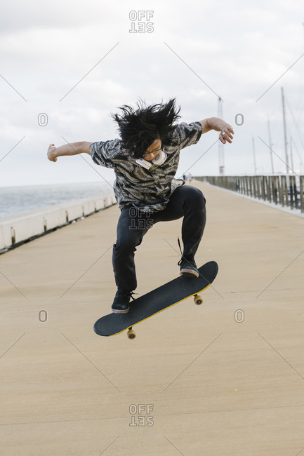 Young man with skateboard performing stunt on promenade against sky