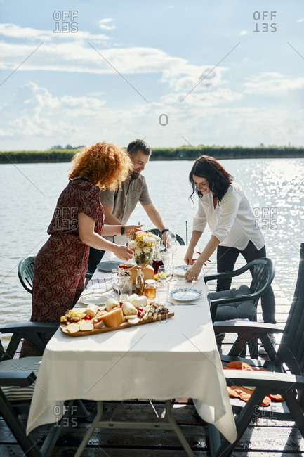 Friends having dinner at a lake laying the table