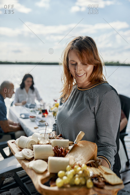 Woman serving cheese platter for dinner with friends at a lake