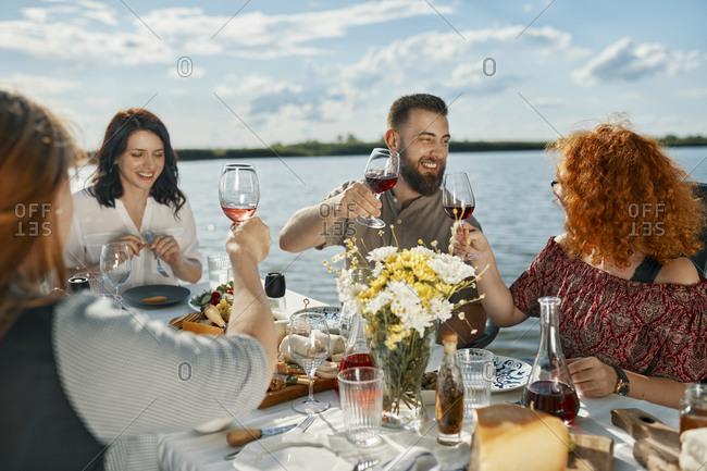 Friends having dinner at a lake raising wine glasses