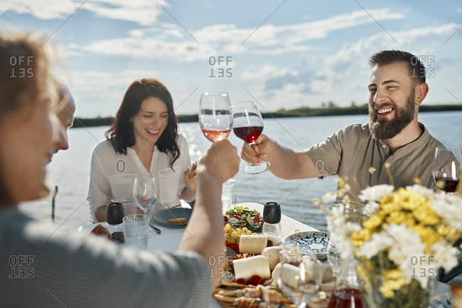 Friends having dinner at a lake clinking wine glasses