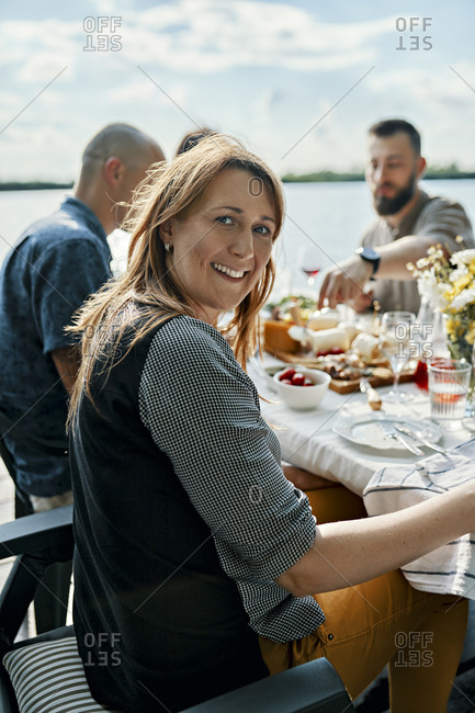 Portrait of smiling woman having dinner with friends at the lakeside