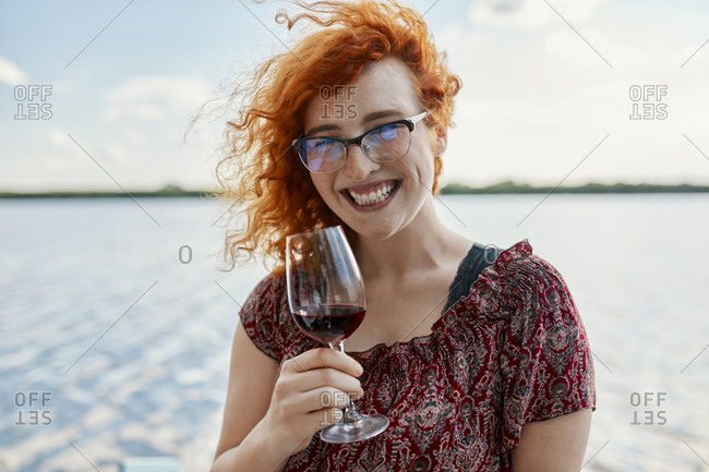 Portrait of happy redheaded young woman drinking wine at a lake