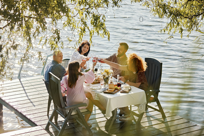 Friends having dinner on jetty at a lake clinking wine glasses