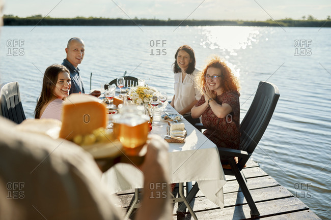 Friends having dinner at a lake with man serving cheese platter
