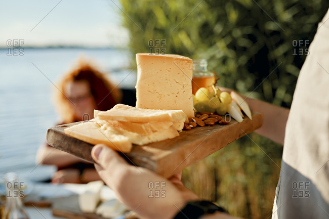 Man serving cheese platter for friends at a lake