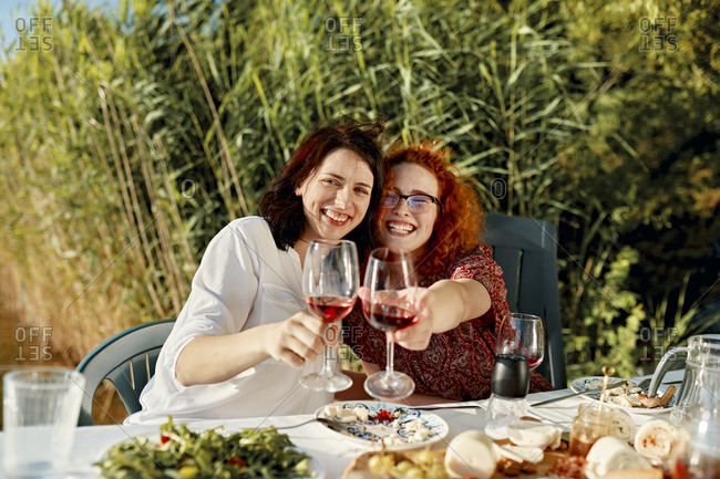 Portrait of two happy female friends having dinner at the lakeside raising wine glasses