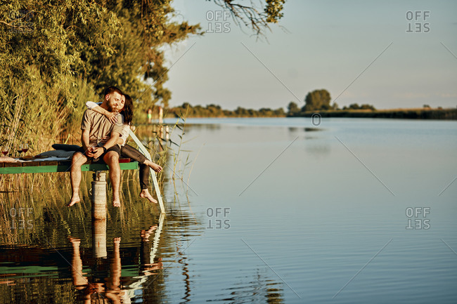 Affectionate couple reflected in water sitting on jetty at a lake