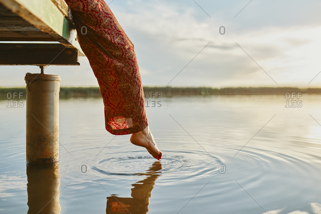 Woman sitting on jetty at a lake at sunset touching the water with her foot