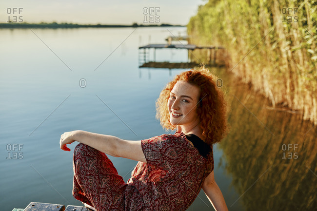Portrait of smiling redheaded young woman sitting on jetty at a lake at sunset