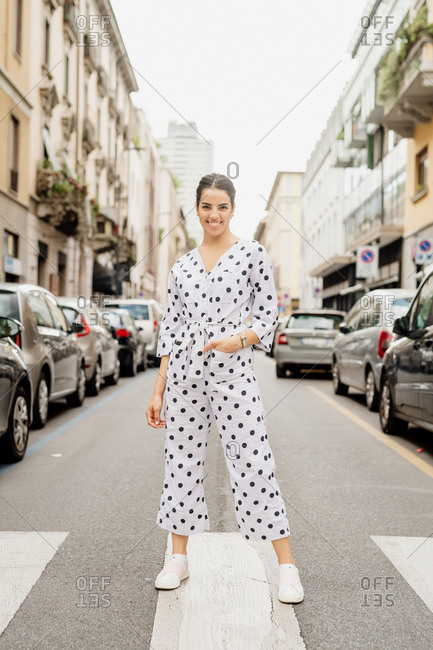 Portrait of smiling woman wearing white and black polka dot jumpsuit, standing on pedestrian crossing.