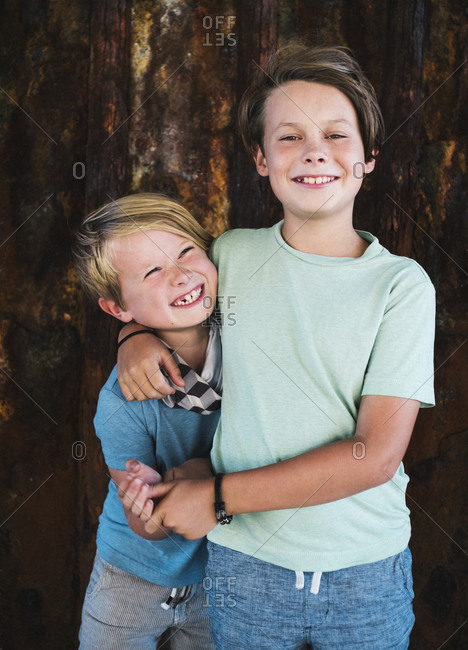 Portrait of two smiling boys, arm around shoulder, looking at camera.