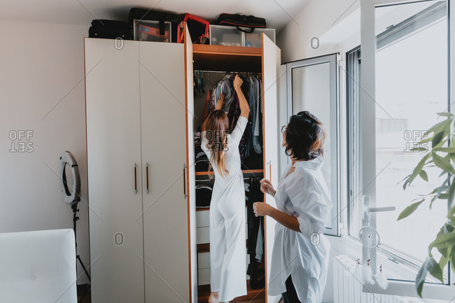 Two women with brown hair standing in an apartment, hanging clothes in wardrobe.