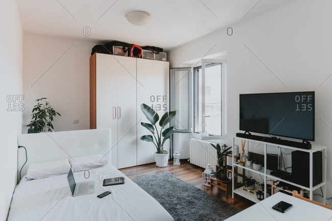 Interior view of living room with wooden floor, white daybed and flat-screen TV on white shelving unit.