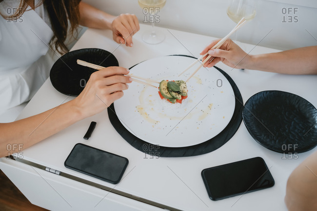 High angle close up of two women sitting at a table, eating sushi.