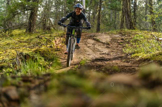 Woman mountain-biking in a forest in the Canadian mountains in British Columbia.
