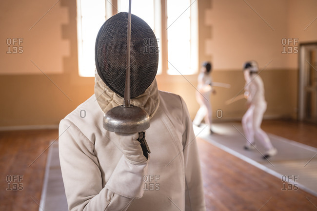 African American sportsman wearing protective fencing outfit during a fencing training session, preparing for a duel, holding an epee in front of face. Other fencers training in the background.