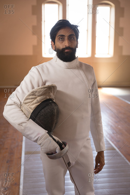 Portrait of mixed race sportsman wearing protective fencing outfit during a fencing training session, looking at camera, holding an epee. Fencers training at a gym.