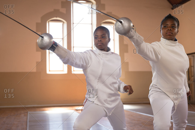 African american sportswomen wearing protective fencing outfits during a fencing training session, holding epees and lunging in unison. fencers training at a gym.