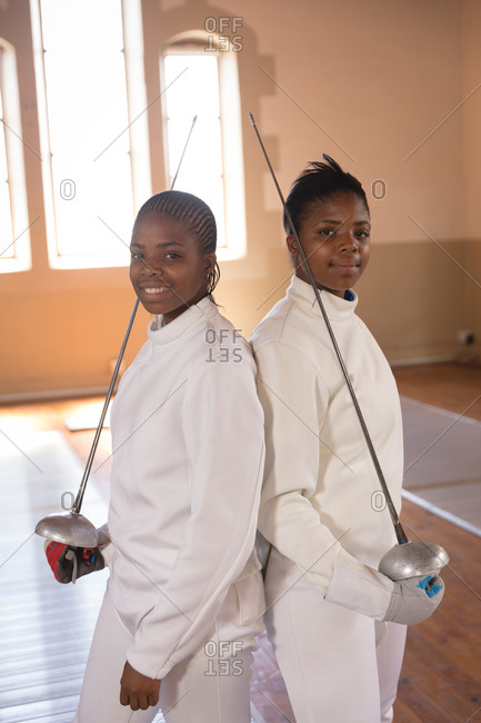 Portrait of two African American sportswomen wearing protective fencing outfits during a fencing training session, looking at camera and smiling, holding epees. Fencers training at a gym.