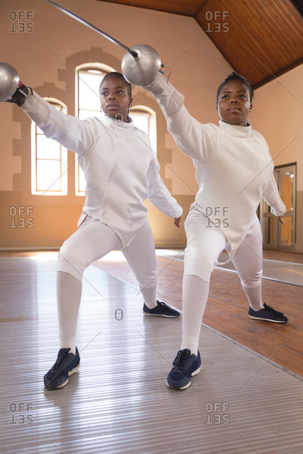 African american sportswomen wearing protective fencing outfits during a fencing training session, holding epees and lunging in unison.fencers training at a gym.