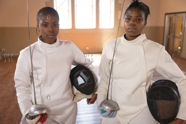 Portrait of two African American sportswomen wearing protective fencing outfits during a fencing training session, looking at camera, holding epees. Fencers training at a gym.