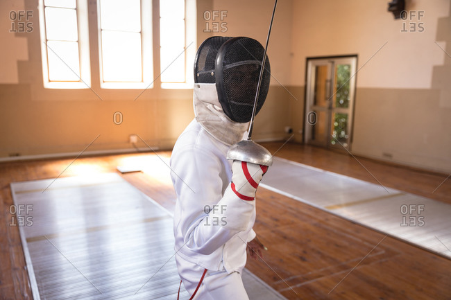 Caucasian sportswoman wearing protective fencing outfit during a fencing training session, preparing for a duel, holding an epee in front of face. Fencers training at a gym.
