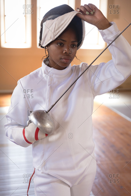 African American sportswoman wearing protective fencing outfit during a fencing training session, preparing for a duel, holding an epee and raising her mask. Fencers training at a gym.