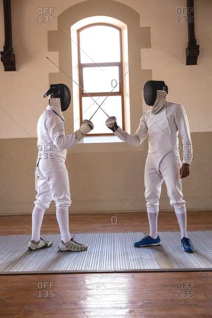 Caucasian and a mixed race sportsmen wearing protective fencing outfits during a fencing training session,standing with their epees crossed. fencers training at a gym.
