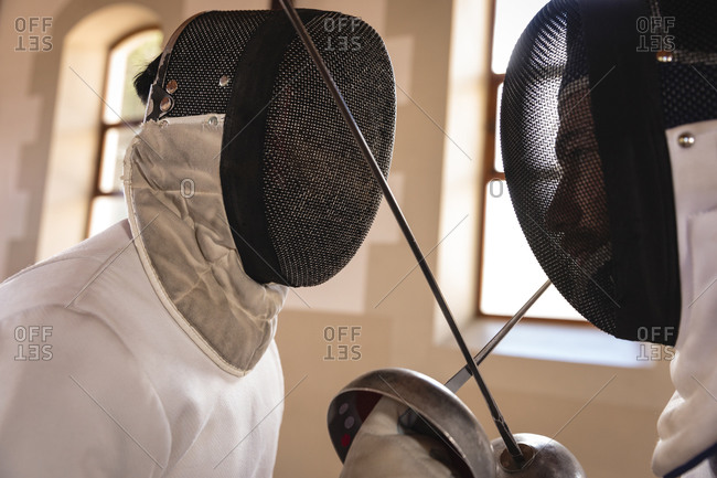 Caucasian and a mixed race sportsmen wearing protective fencing outfit during a fencing training session, facing each other, crossing their epees. Fencers training at a gym.