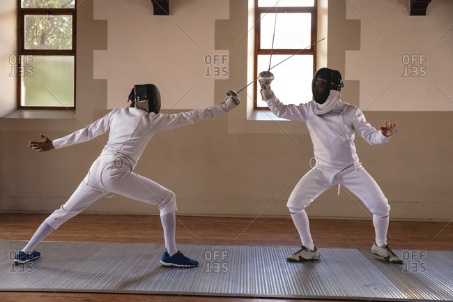 Caucasian and a mixed race sportsmen wearing protective fencing outfit during a fencing training session, taking aim at each other and lunging with their epees. Fencers training at a gym.