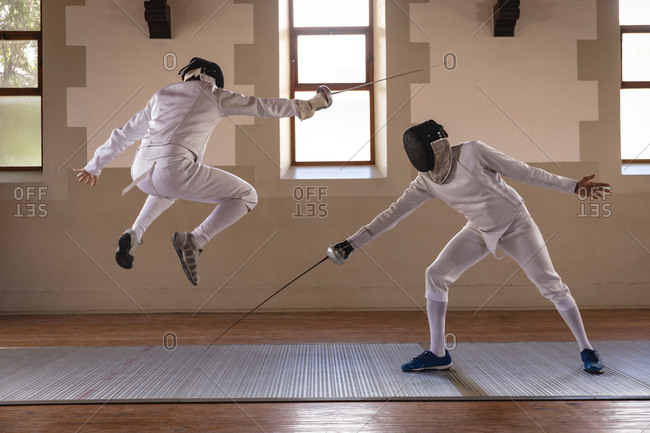 Caucasian and mixed race sportsmen wearing protective fencing outfits during a fencing training session jumping while dueling with their epees. Fencers training at a gym.
