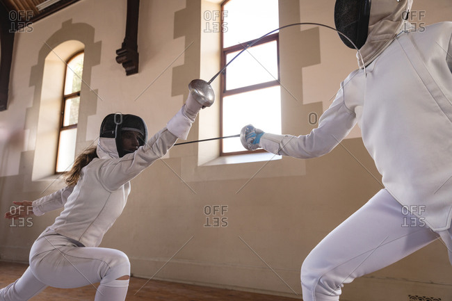 Caucasian and African American sportswomen wearing protective fencing outfits during a fencing training session, taking aim at each other with their epees. Fencers training at gym.