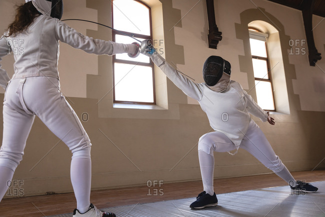 Caucasian and African American sportswomen wearing protective fencing outfits during a fencing training session, lunging at each other with their epees. Fencers training at gym.