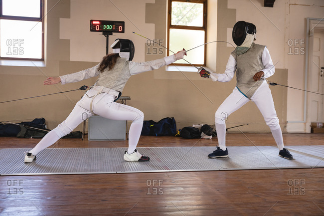Caucasian and African American sportswomen wearing protective fencing outfits during a fencing training session, jumping taking aim at each other with their epees. Fencers training at gym.