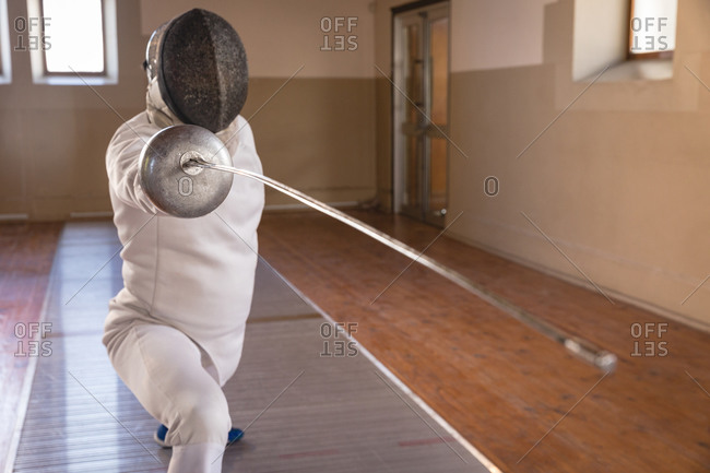 Caucasian sportsman wearing protective fencing outfit during a fencing training session, preparing for a duel, holding an epee and lunging. Fencers training at a gym.
