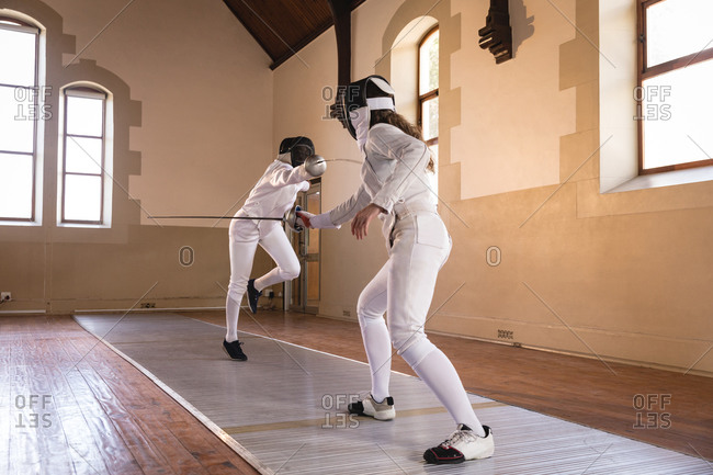 Caucasian and African American sportswomen wearing protective fencing outfit during a fencing training session, dueling with their epees. Fencers training at gym.