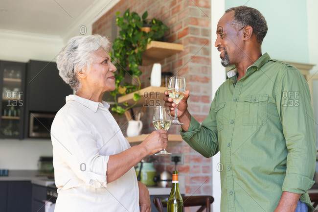 Happy senior retired African American couple at home, smiling and making a toast with raised glasses of white wine, couple at home together isolating during coronavirus covid19 pandemic