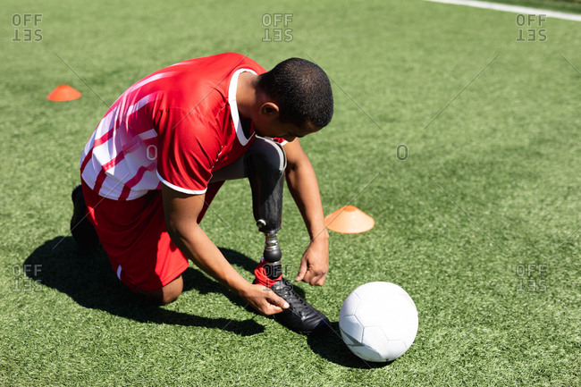 Mixed race male football player with prosthetic leg wearing a team strip training at a sports field in the sun, tying shoelaces ball next to him.
