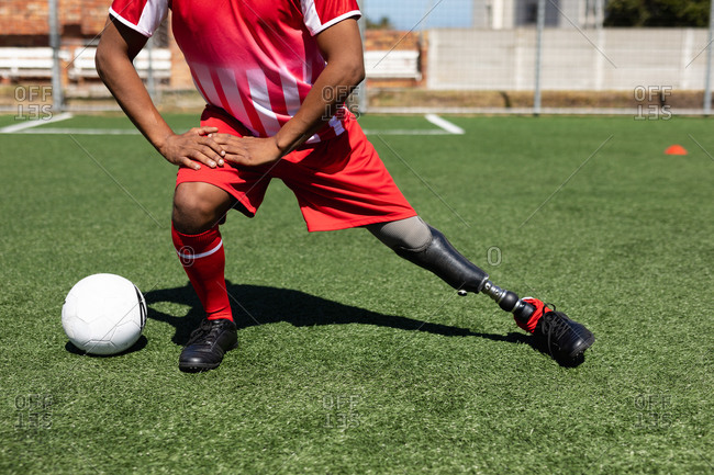 Low section of mixed race male football player with prosthetic leg wearing a team strip training at a sports field in the sun, warming up stretching legs with ball next to him.