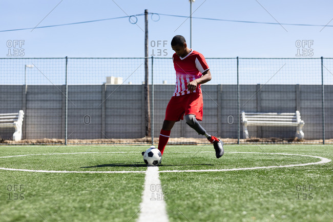 Mixed race male football player with prosthetic leg wearing a team strip training at a sports field in the sun, warming up kicking ball.