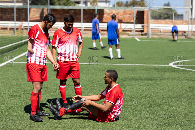 Two multi ethnic teams of male five a side football players wearing a team strip playing a game at a sports field in the sun, player with prosthetic leg sitting player without arm talking to him.